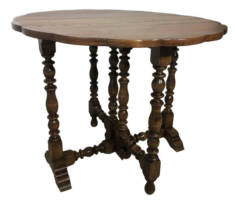 English oak gateleg table with a beveled edge around the top following down to a simple apron and hand-turned barley twist legs, joined by simple stretchers and raised on turned feet, circa 1900.  The top open measures 36.61 x 19.25in.