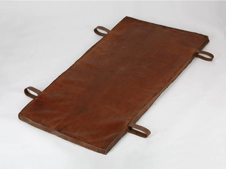 This gymnastics mat from the 1940s was salvaged from an old gymnasium in Prague. The thick cow leather was impregnated and all sides sewn again. The carrying handles were added. Fully customizable beautiful vintage condition.