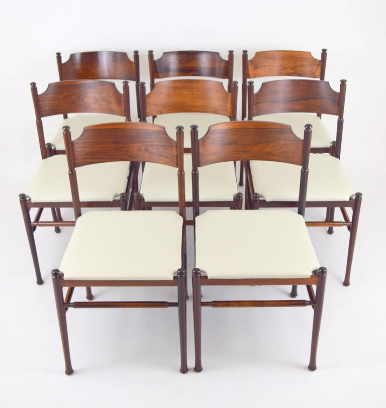 Elegant set of eight rosewood dining chairs in the manner of Osvaldo Borsani. Delicate and light in scale with turned elements and curved plywood backs. Each has a handmade quality with slight variations in wood thickness on backs. Newly upholstered