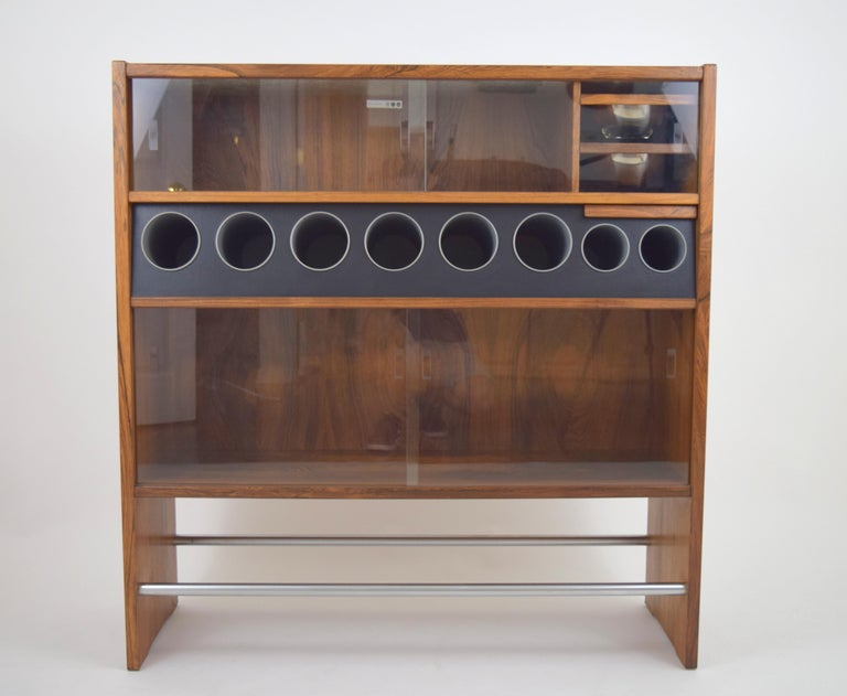 Highly functional rosewood dry bar by Erik Buch. Beautifully grained rosewood case with varying sized bottle storage tubes, two pull-out removable stainless steel bowls, pull-out tray, Two stainless steel foot rest bars, and two open storage areas