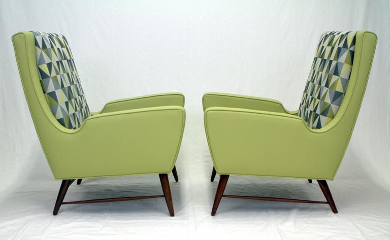 Fantastic pair of Italian lounge chairs upholstered in Ponti style diamante fabric and leather. Expressive forms give these chairs an exciting presence and shape resting on walnut doweled legs with delicate stretchers.