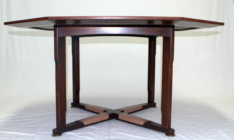 Amazing octagonal walnut game table with an inlay rosewood star by Edward Wormley for Dunbar Janus Collection. Walnut frame reminiscent of Arts and Crafts with original inset leather footrests finished with brass leveler feet. Superior construction