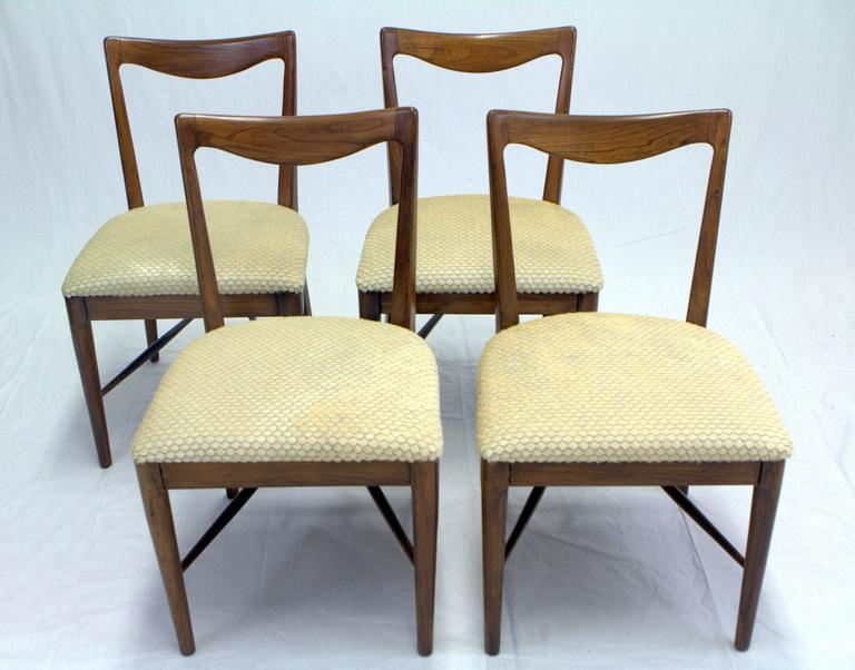 Sculptural set of four Italian walnut dining chairs with laser-cut scalloped hide seats in the style of Paolo Buffa.