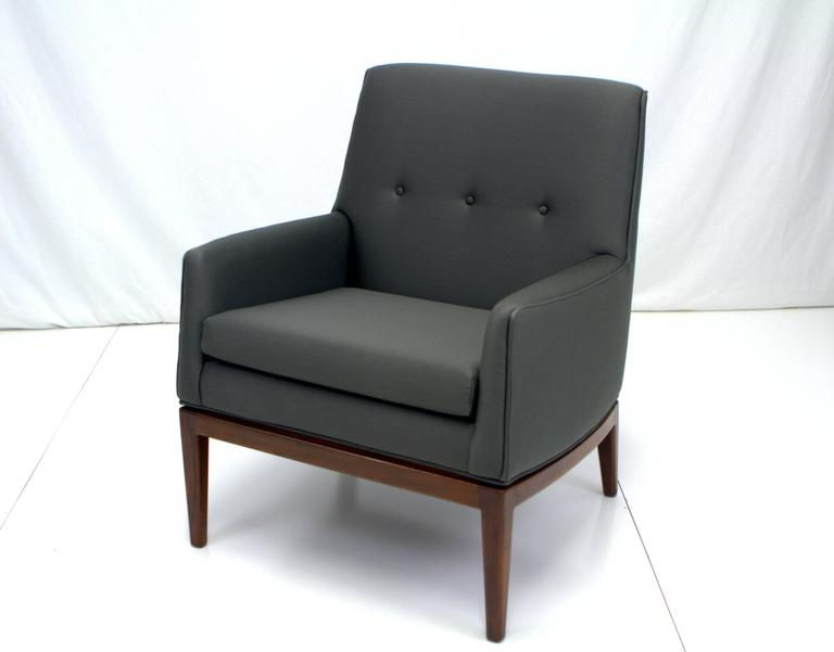 Exceptional Jens Risom walnut base lounge chair upholstered in charcoal wool. Graceful lines with slight bowed sides to angled back appear to float on walnut base. Retains original fabric tag.