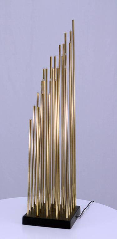 """Amazing light sculpture consisting of 25 slender brass tubes with miniature bulbs emanating from a square ebonized wood base. Measures: 5/16"""" diameter brass tubes range in height from 15"""" to 31"""" graduated to form a diagonal diamond shape."""