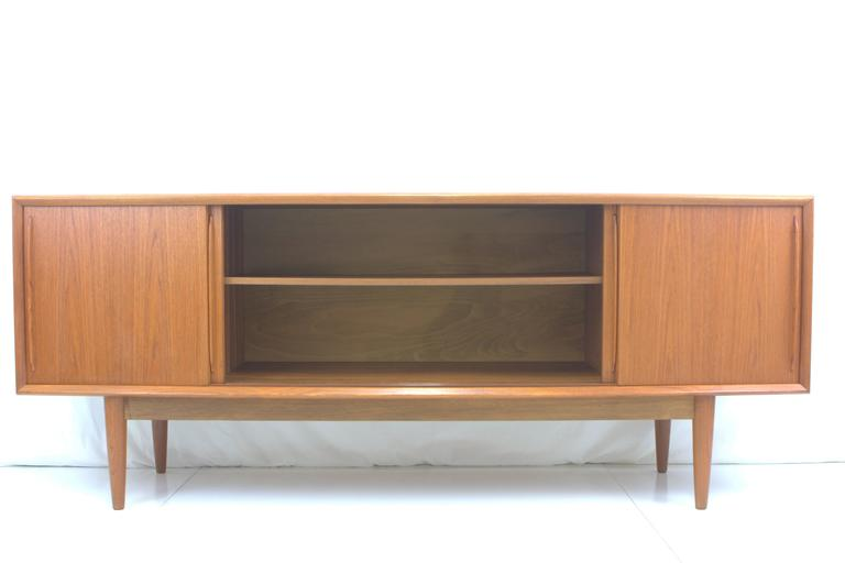 Danish teak perfection. Graceful bowfront credenza by Arne Vodder for H.P. Hansen, Denmark, circa 1960s. Open storage with adjustable shelves behind sliding doors in middle and right side with four shallow drawers on left, one drawer divided for