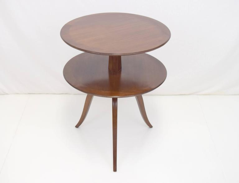 Elegant round tiered table by Edward Wormley for Dunbar. Banded edge surfaces in mahogany with gently curved legs.
