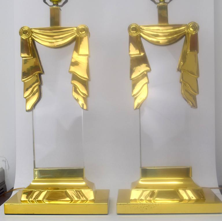 Fantastic pair of lucite and brass lamps in square column style with swag motif.  Reminiscent of Karl Springer designs and superior quality. Polished brass with minor patina and wear, lucite clear and free. Electrical cord enters base then travels