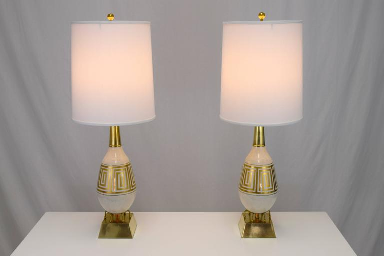 Amazing pair of ceramic and brass lamps with a Greek key motif. Egg shaped ceramic body in a cream and gold speckled glaze with gold leaf Greek key band. Six armed ball feet rocket ship like base resting on pyramidal block in brushed brass. Height