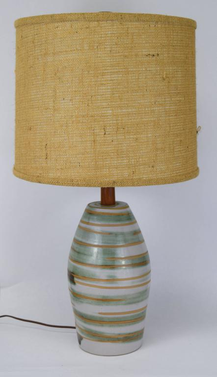 Medium size Marshall Studios swirled glaze table lamp with teak accents. Lovely green, cream, tan swirls to base with incised signature and original UL sticker to socket. Measures: 15.5