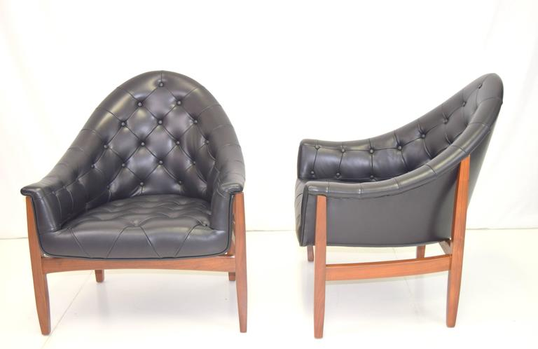 Rare pair of walnut framed tufted chairs by Milo Baughman. Professionally rebuilt and upholstered in black leather and refinished walnut frames. Sexy silhouettes and scale.