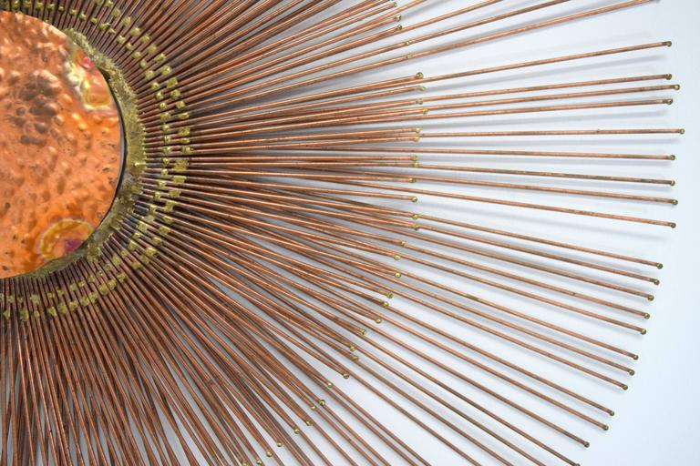 Striking copper wall sunburst wall sculpture by Curtis Jere. Two tiers of copper rods radiate around a central copper textured disc creating multi-level structured composition. Measure: Outer ring rays 29.25