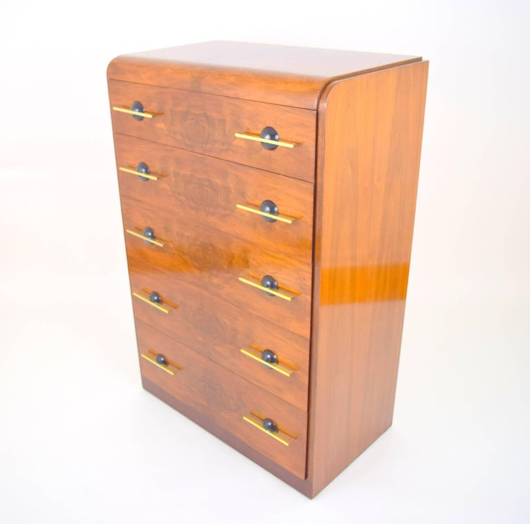 Stunning streamlined moderne chest of drawers by Donald Deskey. Walnut case with five waterfall burl wood front drawers with solid brass bar pulls through hemispherical ebonized wood back plates. Elegant and functional early American modernism in
