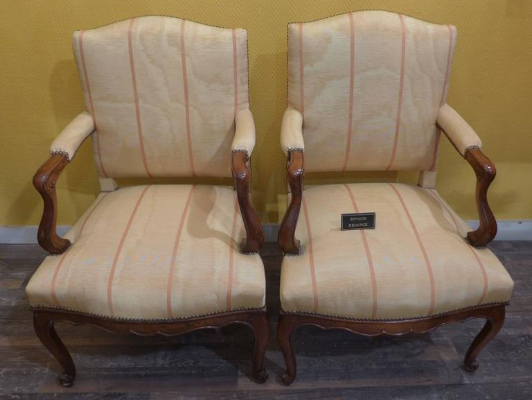 A large pair of armchairs in walnut, dating from the French Regence period, circa 1730.