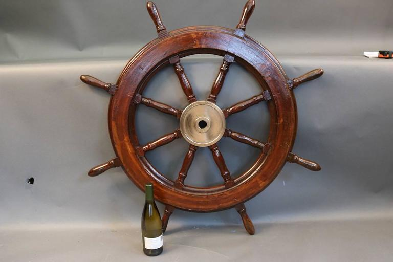 Authentic eight-spoke wooden ship's wheel with a heavy brass hub and a varnished finish.