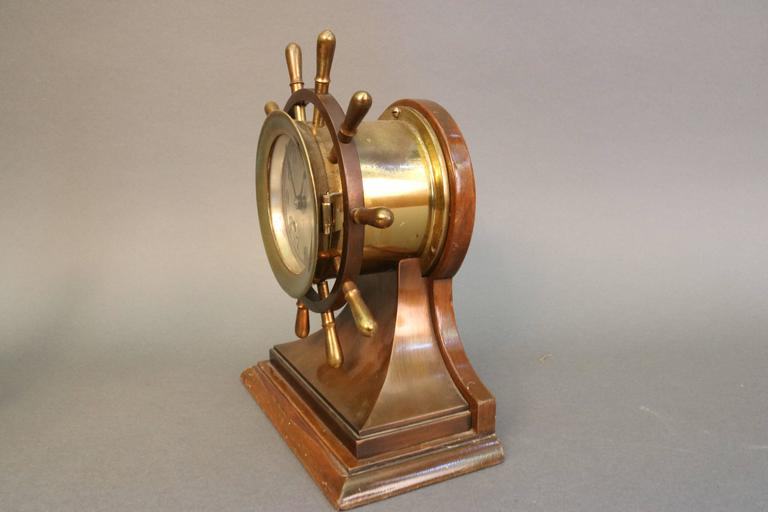 """An American 20th century 3-1/2 inch ship's wheel clock unsigned and in the form of a Chelsea """"Mariner."""" The clock features a slivered face, blackened Arabic numerals, simple hands, double barrel key winds for the movement and the strike,"""