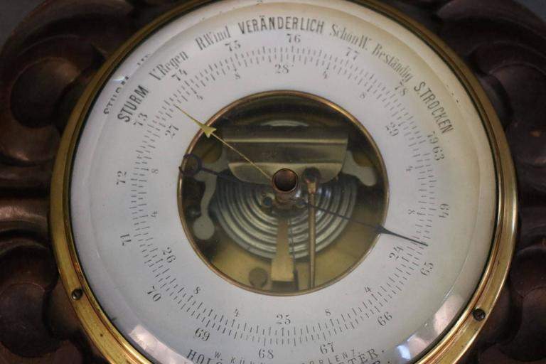 """Polysteric barometer with carved wood backing. Readings in German. Manufacturered by W. Kuhanu Coblenz. Dimensions: 5"""" face D x 11"""" x 8"""" with base."""