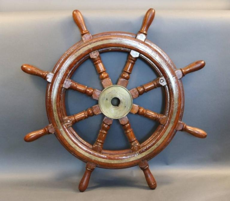 """Brass and mahogany ship's wheel with eight turned spokes. The wheels outer rim is inlaid with brass trim. Heavy brass hub has a full cap.  Overall dimensions: 32"""" diameter."""