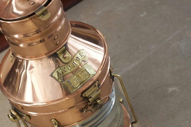 Copper and brass ship's anchor light with hoisting handle, made by the venerable English firm