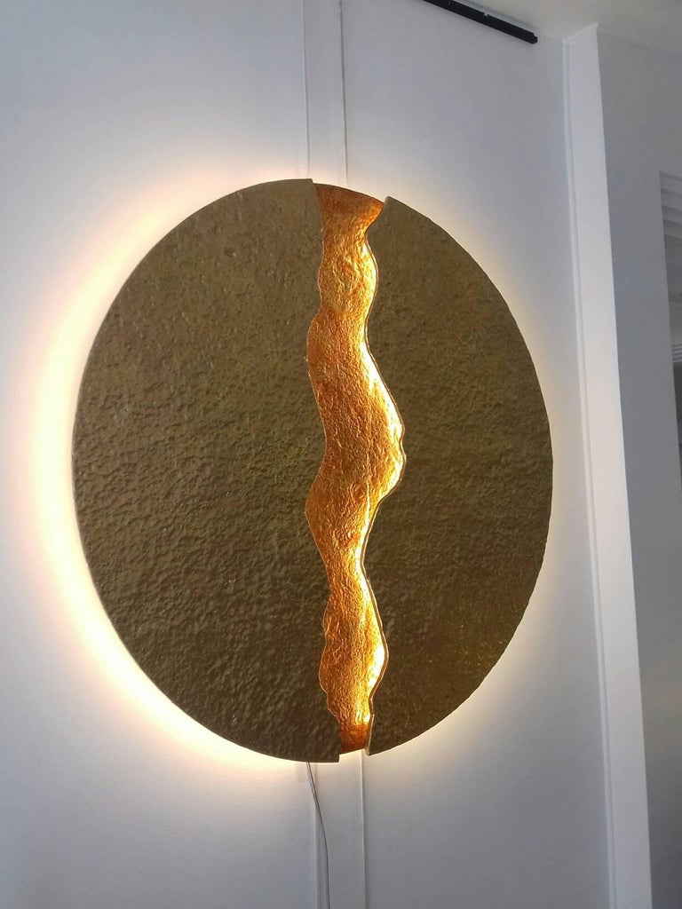 Round wall light, simulating a volcanic lava flow, illuminated on each side of the crack and all around the circle by leds. Double patina gold and orange.