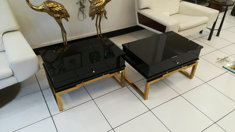 Pair of bedsides or end tables in lacquered wood, brass feet, circa 1970.