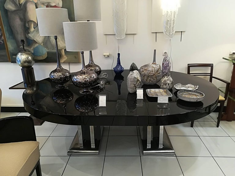 Spectacular dining room table. Original nickel-plated metal base. Black wooden lacquered top. The top opens and comes with two extensions of 50 cm each one, circa 1935.
