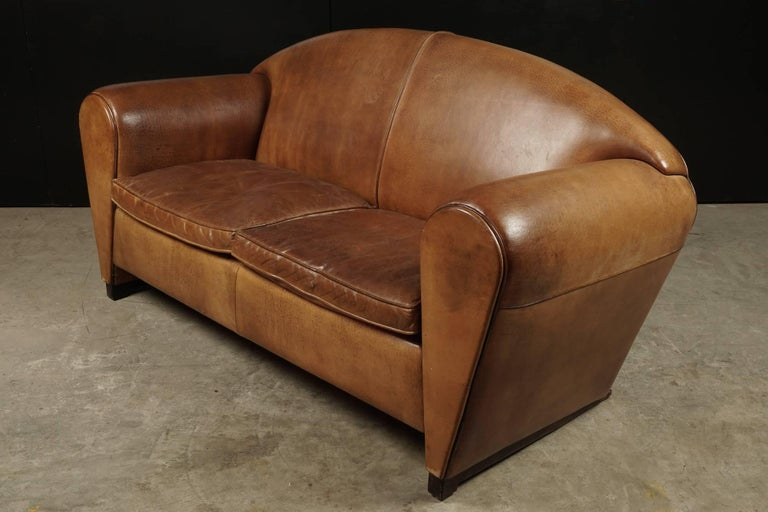 Rare Mid Century Leather Sofa From the Netherlands, Circa 1970.  Superb design in cognac leather with piping.  Feet covered in leather.