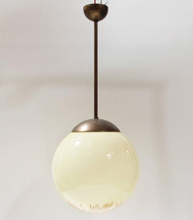 Italian Murano Anemone glass globe pendants with bronzed metal hardware / Designed by Ludovico Diaz de Santillana for Venini circa 1960's / Made in Italy 1 light / E26 or E27 type / max 60W  Diameter: 14 inches / Height: 34 inches including rod and