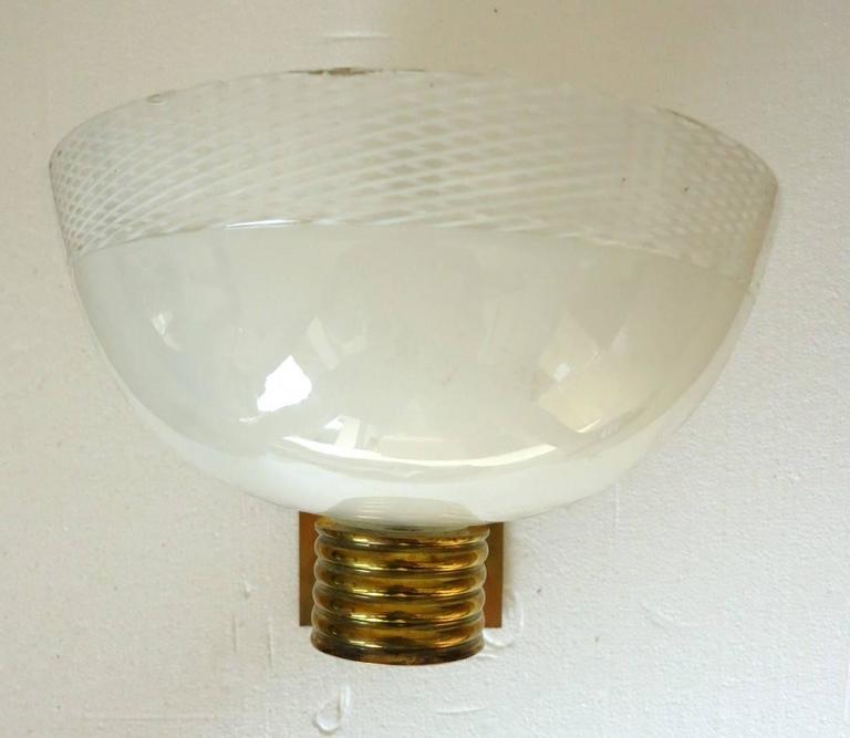 Vintage wall lights by Venini with Murano ribbed white glass bowl shades mounted on brass arms and backplates.