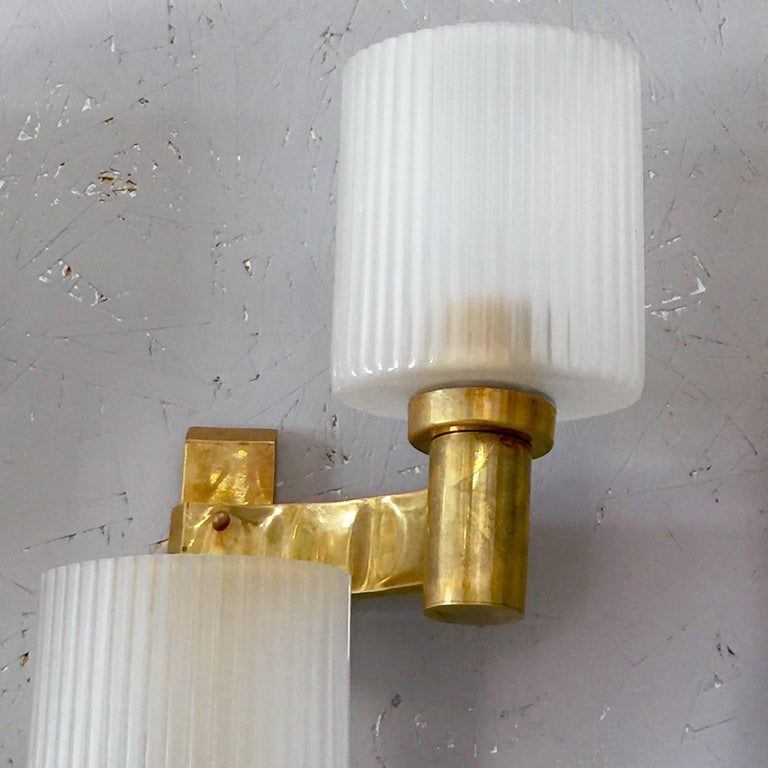 Vintage Italian wall lights with three frosted Murano glasses with textured ribbed vertical details mounted on brass frames / Designed by Stilnovo, circa 1960s / Made in Italy 3 lights / E26 or E27 type / max 60W each Height: 27 inches / Width: 13