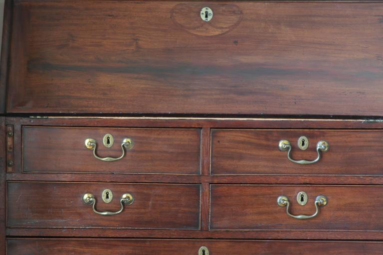 Outstanding late 18th century mahogany secretary bookcase in very good condition. The doors open to reveal three adjustable shelves, 15 various sized drawers, dentil molding, and a green tooled leather writing surface. Base shows two over four