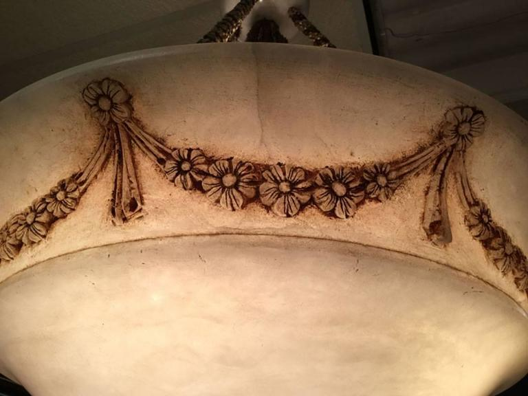 Large alabaster pendant with highlights floral swag around edge. Light is suspended by thick woven roping. White ceramic ceiling mount. Height of main light is 10