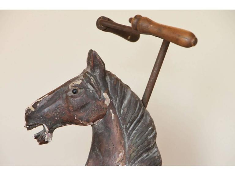 Antique Folk Art horse form tricycle with paint decoration having rustic iron frame, wood handles. Condition: One stirrup broken off and included, repair to front leg, flaking paint; consistent with age. Working condition.