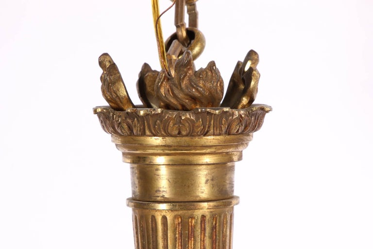 A torch form standard with upright flames and attached six-horn form lights. An acanthus leaf terminal and shaped chain links. With 10 inch of chain.  Condition: Heavily tarnished. No ceiling cap.
