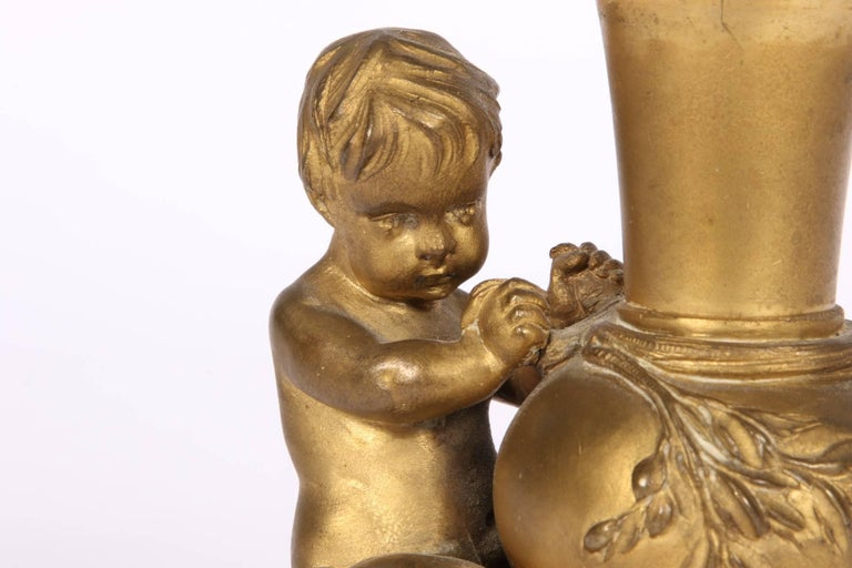 A putto seated at a tall necked vase with raised leafy branch. Mounted on a textured oval base. Signed on the base. Condition: very good with some wear to the still nice patina.