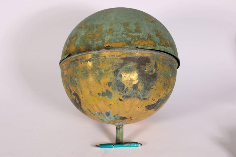 Globe form made in two parts, with a hollow stem for attachment on the base.  Worn gilt, patches of green patina overall, separation around the center seam, ding, all as expected with use.