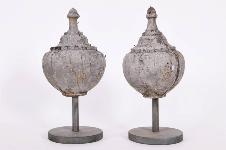 In a weathered grey paint. Mounted on stands. Condition: cracks through the centres, overall weathered paint.