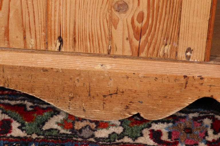 In knotty pine with a carved top over an openwork band and two open shelves. The lower cabinet with one apron drawer and double doors with a tab closure, all with brass knobs. A carved shaped base in front.  Condition: chips to the top corners,