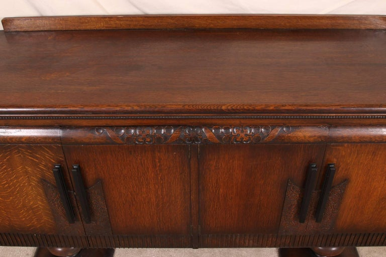 With a back splash, two double doors with carved top bands, floral plaques with ebonized handles, and reeded lower bands. The interiors with a single recessed shelf and drawer on each side. The cabinet with recessed side panels, and raised on