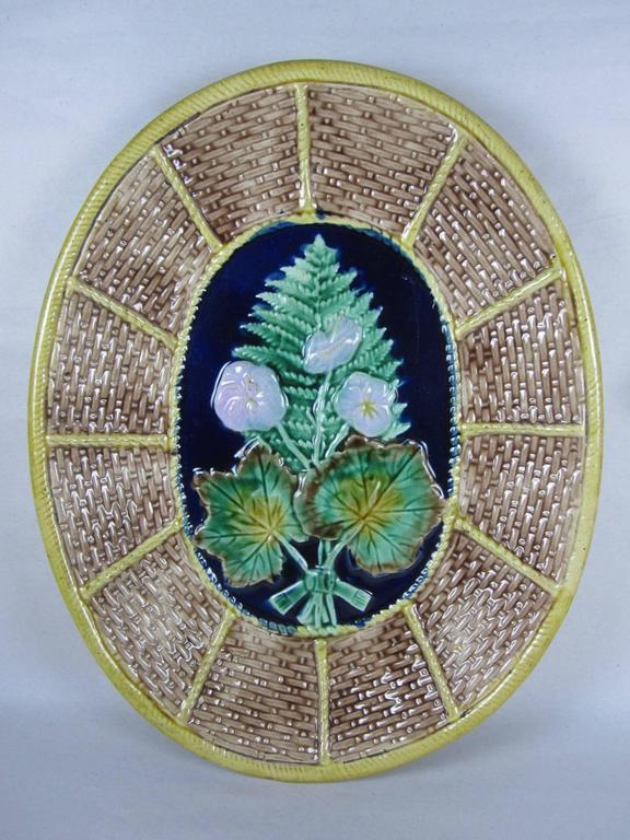 In incredible antique condition, a 19th century English Majolica glazed oval serving platter or cheese board, showing a fern and floral pattern on a woven basket ground. The wicker motif is commonly seen in platters made for serving cheeses.