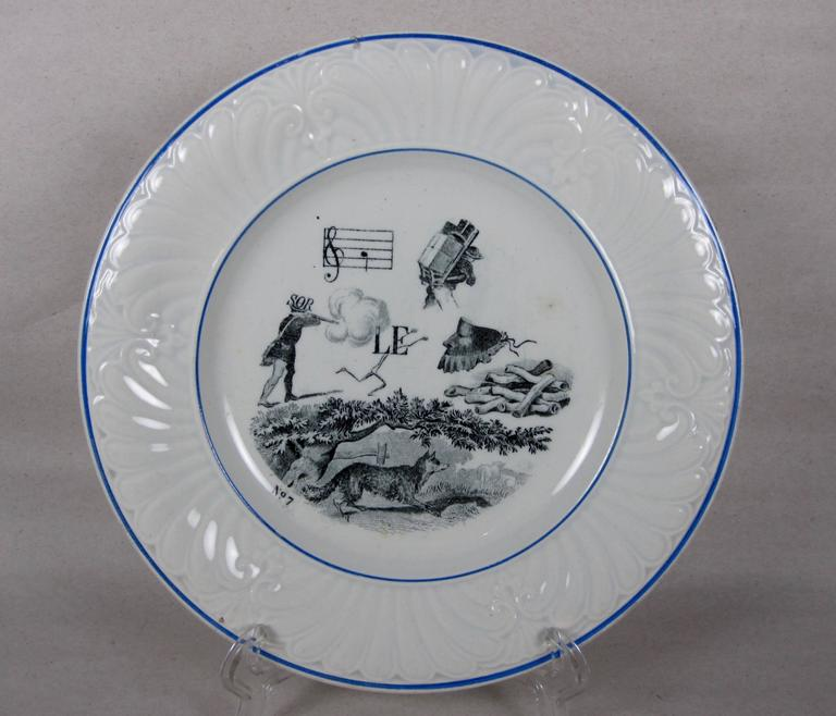 A set of six French Rebus Puzzle dessert plates, transfer printed in black on a white earthenware body. When solved, the picture puzzle spells out a wise saying or maxim.  From the early 1800s-early 1900s, most French homes had a set of Rebus