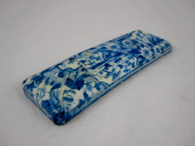 A transfer printed pearlware glazed knife rest, Staffordshire, circa 1820. A lovely overall floral and pastoral sheet pattern. Indented in the center to hold the blade. These Georgian era smaller pieces are a rarity.