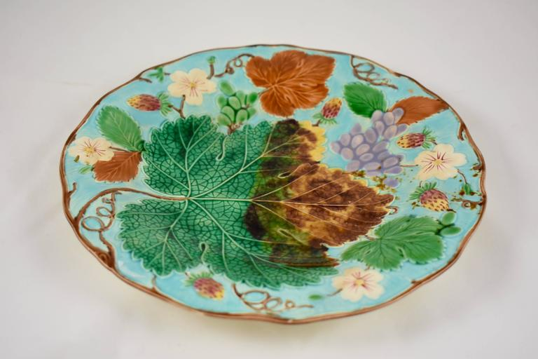 A traditional English grape leaf and strawberry pattern wedgwood Majolica plate, showing a low relief arrangement of grape leaves fruits and flowers, on a bright turquoise ground. Trailing vines form a brown scalloped rim. Hand-painted enameled