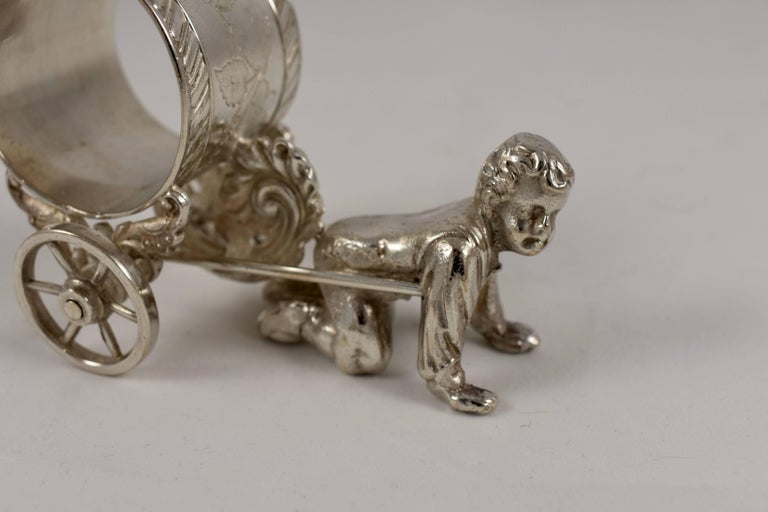 From the Victorian era, a silver plated figural napkin ring showing a young boy pulling a cart that holds the engraved ring. The child is dressed in knickers and a button-down shirt with a bow tied at his collar. The wheels on the cart are
