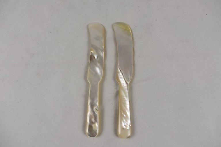 A handcrafted mother-of-pearl spreader, used for serving caviar on toast points.   Mother-of-pearl or animal horn is traditionally used when serving caviar as its texture will not in any way taint the taste or damage the delicate form of the caviar