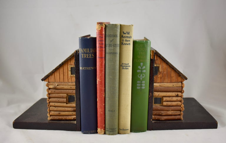 A rustic pair of handmade bookends, formed as log cabins, circa 1930s-1940s.