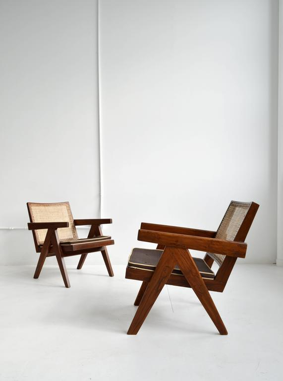 Pair of iconic Pierre Jeanneret teak armchairs with cane back and seat from the Chandigarh administrative buildings in India, 1950s. Jeanneret's simplistic design highlights the inherent beauty and integrity of his materials and convey a refined,
