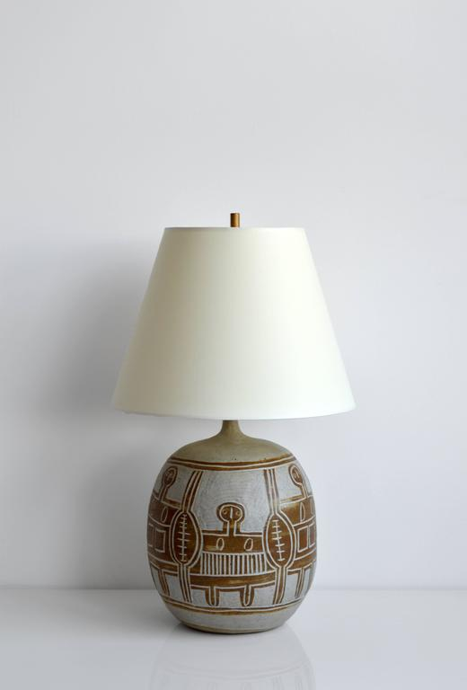 Vintage French ceramic table lamp. Carved figural artwork surrounds the base. This lamp has been rewired for US use with a brown silk cord. Wonderful for any bedside table or case piece.