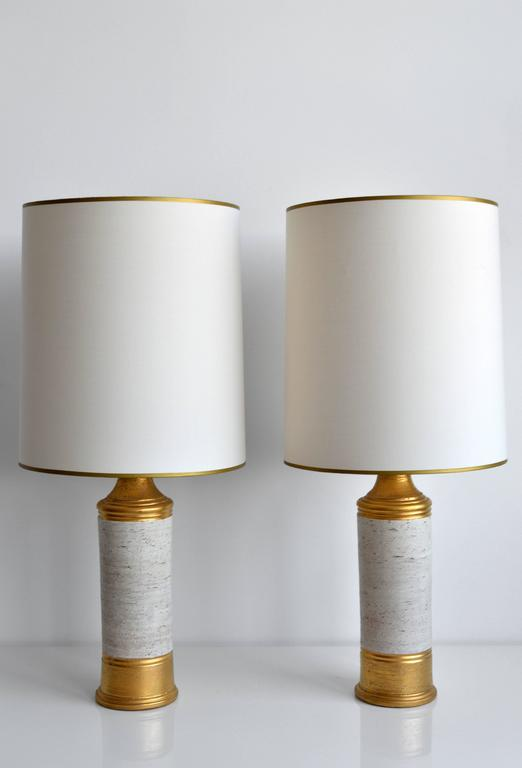 Pair of vintage table lamps by Italian ceramics company Bitossi for Bergboms, circa 1960s. Each lamp has a matte gold finish with an off-white