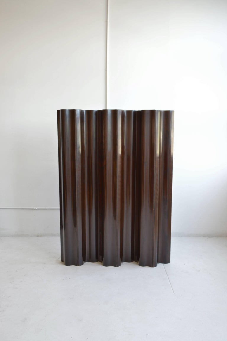 Vintage molded plywood screen by the iconic American designer Charles Eames for Herman Miller in the 1950's. This screen features six panels in a warm, deep mahogany finish attached by a discreet fabric hinge detail. This folding screen or room